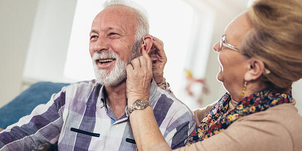 lady checking hearing aid device on a man's ear