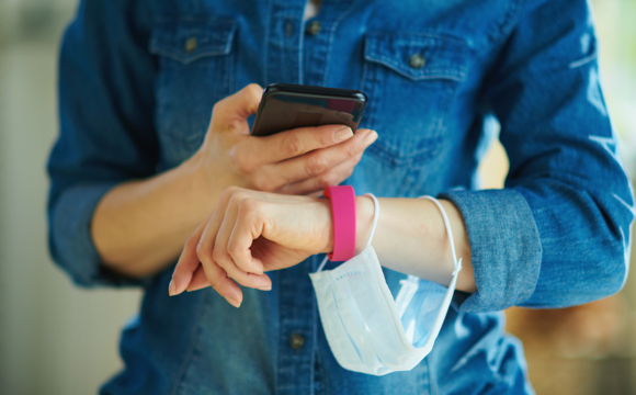 a smartphone and fitness tracker checking stats in the house