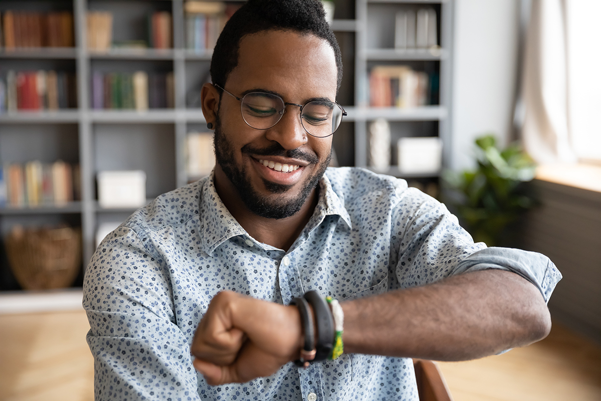 man looking at smartwatch while at home