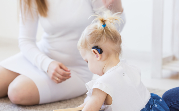 Toddler child wearing a hearing aid