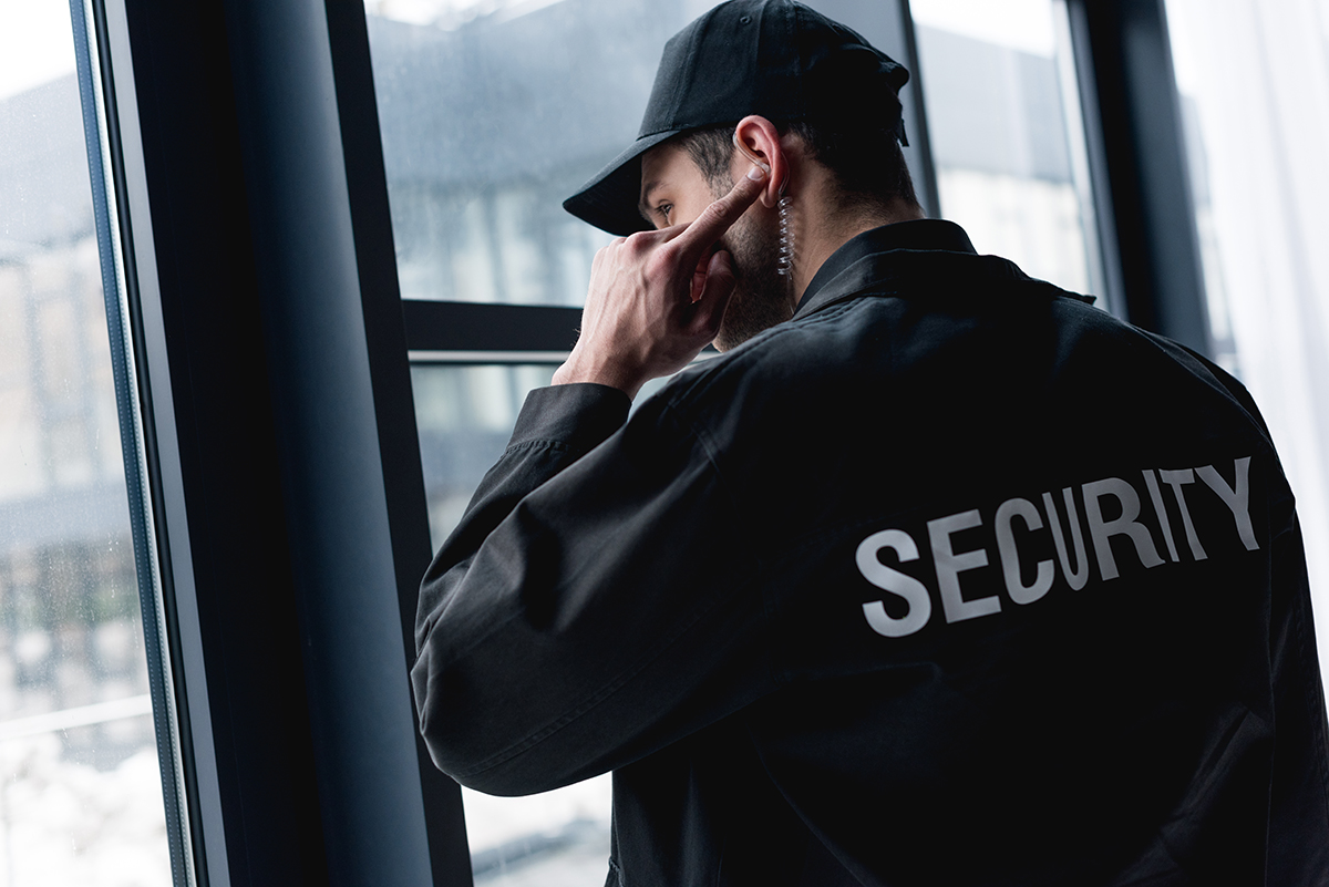 Security Guard wearing jacket and hat listening