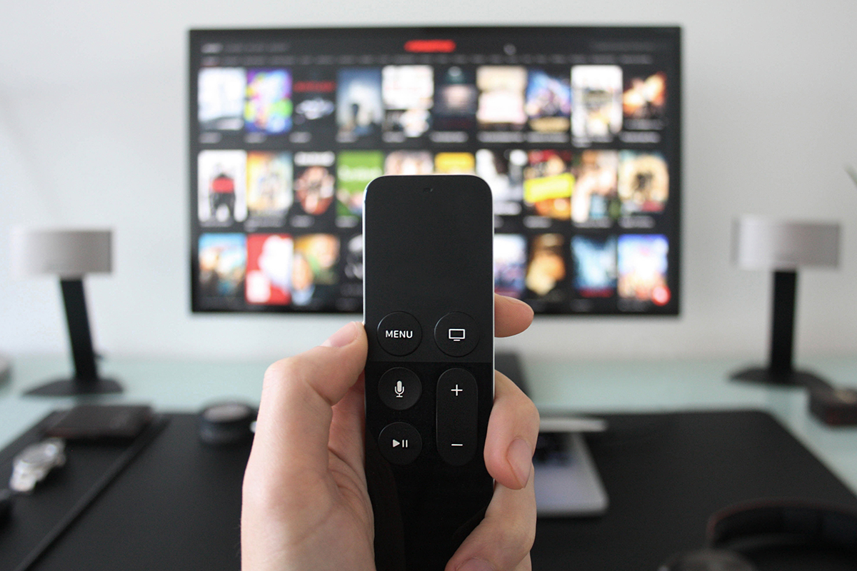 hand holding smart remote controller used to stream movies and shows